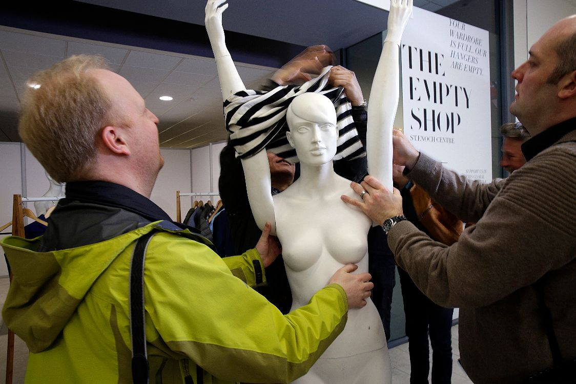 Journalists dressing a mannequin